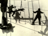 Silhouettes of Workers Using Rope Rigging to Clean and Paint the Side of a Ship