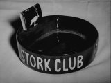 Stork Club Ashtray with a Stork Emblazoned Book of Matches on Table in This Exclusive Night Club