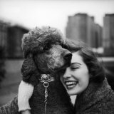 Woman Profiling a Big Smile While Adoring Her Poodle Wearing Large Swiss Watch on Dog Collar