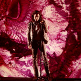Rock Star Jim Morrison of The Doors Singing on Stage in Front of a Purple Psychedelic Backdrop