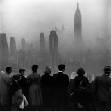 People on Top of a Building Looking Down Into Downtown Misty Smog covering Empire state Building