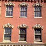 Brick Facade of 19th Century Building with Ornate Stonework Around Windows