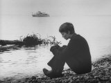 Actress Mia Farrow Pensively Sitting on Rocky Shore of Lake Geneva as Passenger Boat Passes By
