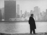 William J Zeckendorf walking alongside East River with the United Nations Building in background