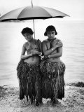 Young Yap Island ladies sporting traditional Grass Skirts  Sharing umbrella in the Caroline Islands