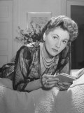 Actress Joan Fontaine Wearing Sheer Negligee While Lounging on Bed at Home
