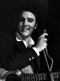 Rock Elvis Presley Performing One of His Hits on Stage During Concert