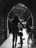 College Co-Ed Walking Bicycle Through an Archway on the Campus of Princeton University