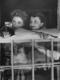 Actress Joan Fontaine with Actress Sister Olivia de Havilland Looking Out of Open Window at Home