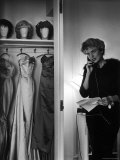 Singer Julie Wilson on Phone Beside Closet with Hanging Evening Dresses and Wigs on Top Shelf