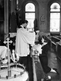 Priest sprinkling Holy Water on baby held by woman in front of altar in Ukrainian Orthodox Church