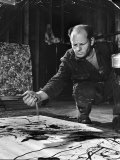 Jackson Pollock Dribbling Sand on Painting While Working in His Studio