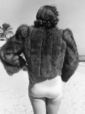 Model Wearing Fur Jacket over Bathing Suit During Walk on Miami's Beac