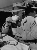 Syndicated Columnist Walter Winchell Clad in Overcoat and Gloves Drinking Coffee in Outdoor Patio