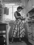 Career Girl Hostedd Joan Wilson in skirt and sleeveless blouse cooking in kitchen