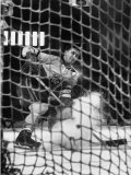 Ice Hockey Player Jean Believeau  Hitting a Puck Into the Goal