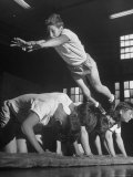 Corner of the Gym at a YMCA  a Boy Heads Into Somersault as He Jumps over Five of His Cohorts