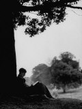 British Author Colin Wilson Sitting Underneath a Tree Wrapped in a Sleeping Bag  Reading a Book