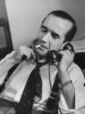 News Commentator  Edward R Murrow with cigarette in mouth  tie loose  resting in his chair