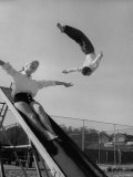 Acrobat and Actor Russ Tamblyn Doing a Flip at a Playground with Movie Actress Venetia Stevenson