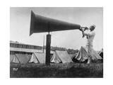 Man Blowing Bugle Into Large Megaphone  with Pitched Tents Behind Him  at US Naval Training Camp