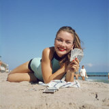 Model Holding Hand of Playing Cards While Relaxing on Beach