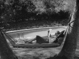 Greer Garson Reading While Relaxing in a Hammock Near Her Pool at Home