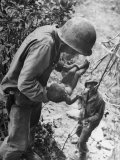 American Lieutenant Carrying Micronesian Baby He Found in cave Japanese Soldiers Holed Up There