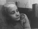 Girl Gazing Pensively Through Pane of Her Apartment Window  Grimly Reflects Image of Berlin Wall