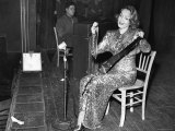 Marlene Dietrich Clad in Sequined Evening Gown Playing a Classical Number on a Saw with Violin Bow