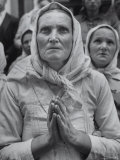 Devout Yugoslav Peasant Woman  Prays with Folded Hands Before a Catholic Shrine to the Virgin