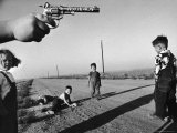 """Boy's Hand Holding a Toy Six Shooter Pistol During a Game of """"Cops and Robbers"""""""