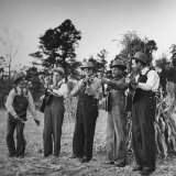 Five Male Musicians Dressed in Hats and Bib Overalls Standing in a Field