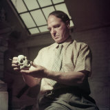 Sculptor Henry Moore Holding a Small Sculpture in His Studio in Much Hadham  England