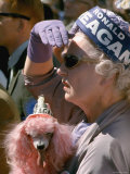 Female Holding Pink Poodle Wearing Hat Emblazoned with Reagan During Campaign Speech
