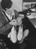 Pop Singer Pat Boone Autographing His White Buck Leather Shoes for Charity