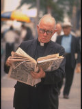 Episcopalian Priest Reading a Newspaper While Walking in Street  New York City