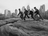 Boys Climbing About on Rock Formation in Central Park as Essex House Looms Amidst Skyline of City