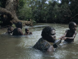 Aborigine Mothers and Children Cool off During a Swim in a River