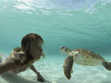 A Young Woman Swimming Face-To-Face with a Green Sea Turtle