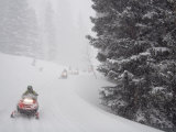 A Group of Snowmobilers Turn a Corner in a Snowstorm
