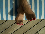Woman's Feet on a Striped Cushion on the Deck of a Cruise Ship