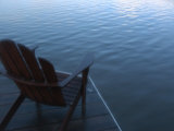 An Adirondack Chair Silhouetted by a Lake
