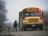 A Student Boards a School Bus in the Morning Fog