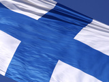 Close-up of the Flag of Finland on White Fabric with a Blue Cross Against Blue Sky