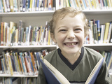 Smiling Little Boy Holding Book in Library