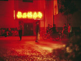 Motorcyclists outside a Karaoke Bar with a Neon Sign in Hunan