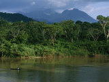 A Canoe Dwarfed by the El Almandro River and Surrounding Rain Forest