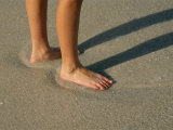 Feet in the Wet Sand of a Beach Wait for the Next Surge of Surf