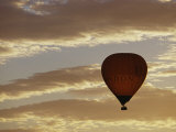 A Soaring Hot Air Balloon against a Cloud-Filled Sky at Dawn